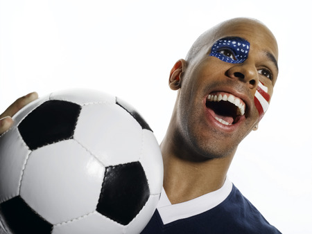 Man with USA flag painted on face, holding football photo
