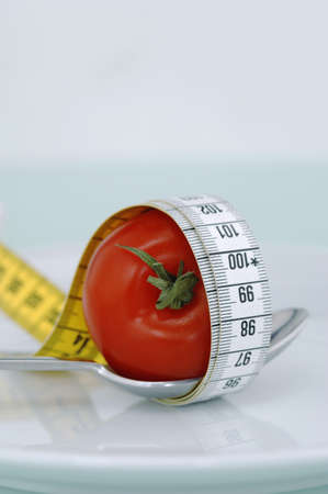 breadth: Tomato on spoon with measuring tape, close-up LANG_EVOIMAGES