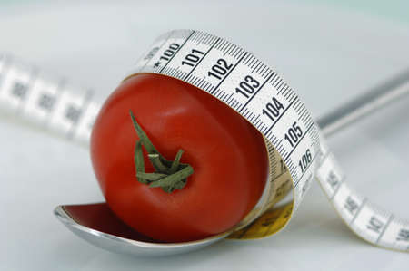extent: Tomato on spoon with tape measure