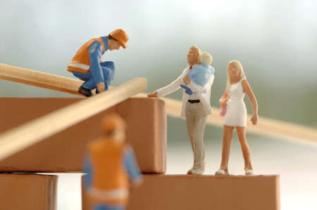 confiding: Figurines of construction workers and family at construction site