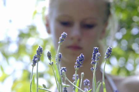 auras: Young woman standing in lavender field, focus on lavender flowers at foreground, close-up