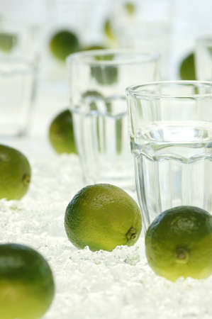 citrons: Lime fruits and water glass on crushed ice, close-up