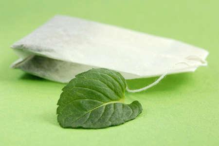 birdseye: Tea bag and mint leaf, close-up LANG_EVOIMAGES