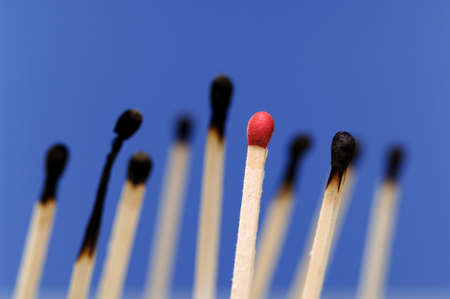 differently: Red match, burned matches in background