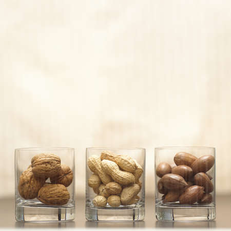juxtaposing: Three different nuts in glasses LANG_EVOIMAGES