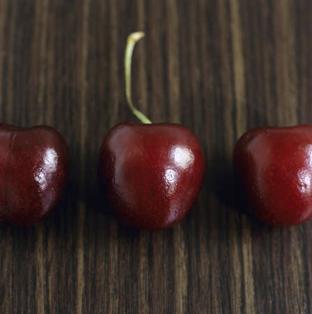 birdseye: Three cherries in row, close-up LANG_EVOIMAGES