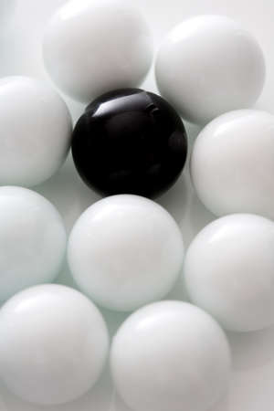 conformance: Black ball between several white balls, close-up
