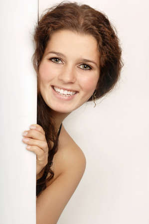 Young woman peeking through door,portrait,smiling