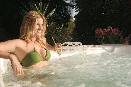 Woman relaxing in whirl pool, holding drink