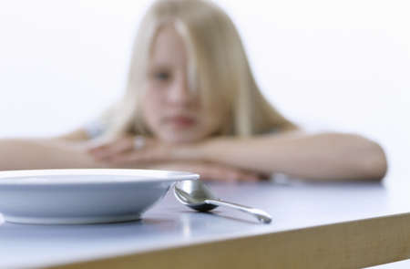 13 15 years: Girl looking at empty bowl