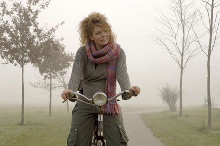 Woman on bicycle in autumn LANG_EVOIMAGES