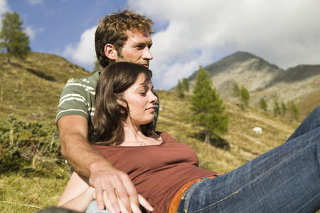 Young couple sitting in meadow in mountains LANG_EVOIMAGES