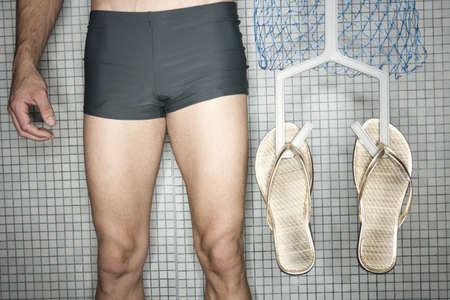 sandalias: Hombre de pie en el cambio de habitación, sosteniendo percha con chanclas, bajo la sección LANG_EVOIMAGES