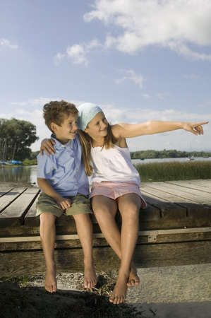 embracement: Boy and girl (6-9) sitting on jetty LANG_EVOIMAGES