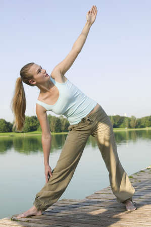 casua: Woman (20-25) exercising yoga on jetty