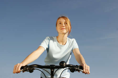age 25 30 years: Young woman on bicycle, low angle view
