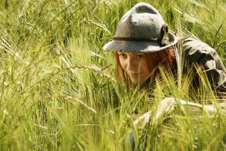 age 25 30 years: Young woman hiding in field looking away, close-up