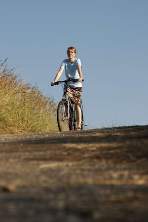 age 25 30 years: Young woman riding bicycle, low angle view