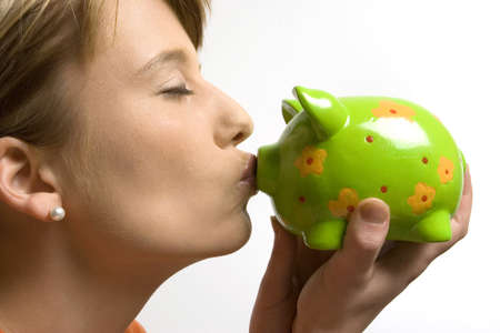 18 20 years: Young woman kissing piggy bank, close-up LANG_EVOIMAGES