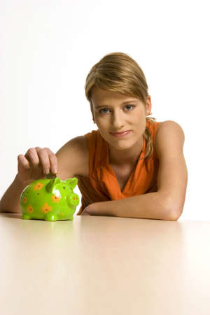 18 20 years: Young woman with green piggy bank, portrait