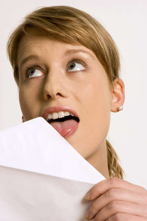 Young woman licking envelope, close-up