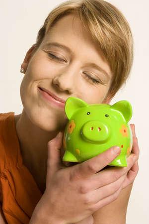 auspiciousness: Young woman embracing piggy bank, close-up LANG_EVOIMAGES