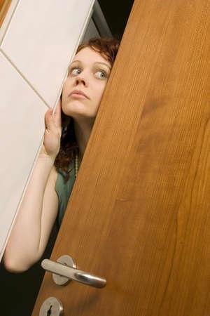 caching: Young woman peeking through door, close-up LANG_EVOIMAGES