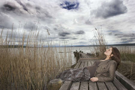 25 30 years: Young woman sitting on jetty,eyes closed,side view