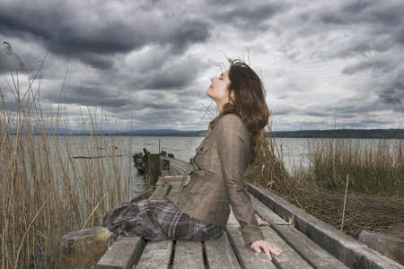 Woman sitting on jetty LANG_EVOIMAGES