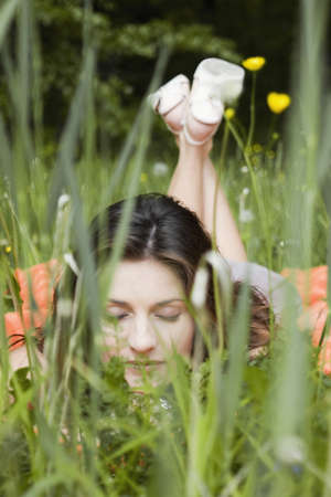 caching: Young woman lying in grass