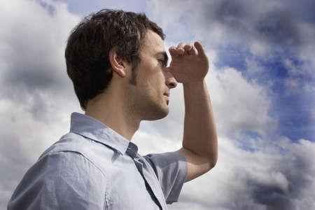 Darkhaired man against cloudy sky,portrait