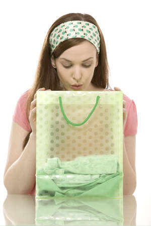 cau: Young woman looking in shopping bag, portrait LANG_EVOIMAGES