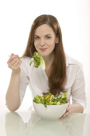 casua: Woman eating a bowl of salad, portrait