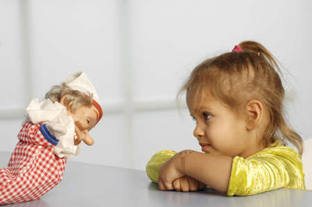 glove puppet: Girl (3-5) looking at glove puppet LANG_EVOIMAGES