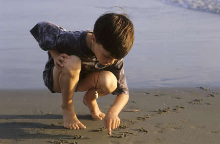 7 9 years: Boy (6-7) writing on sand at beach