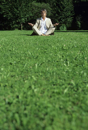 indian style sitting: Mid adult man meditating in park, ground view