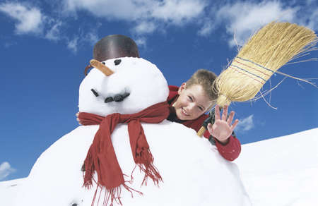 Boy standing behind snowman with broomstick