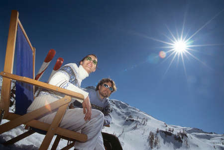 deck chairs: Couple sitting on deck chairs in snow low angle view LANG_EVOIMAGES