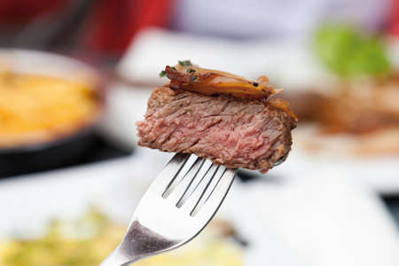 rump steak: Rump steak with stewed onions and herb butter on fork close up