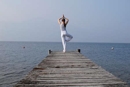tree position: Italy Lake Garda Woman 2025 exercising yoga on jetty