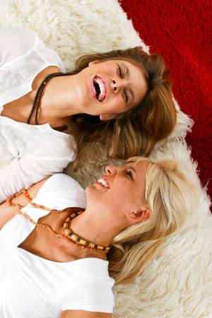 Two woman laughing on floor LANG_EVOIMAGES