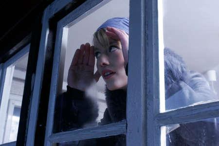 through window: Woman looking through window