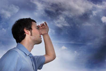 shielding: Young man shielding eyes closeup low angle view