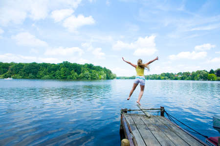 Woman Jumping into Lake rear view LANG_EVOIMAGES
