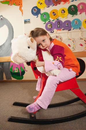 cuddly toy: Germany Girl 34 sitting on rocking horse holding teddy portrait