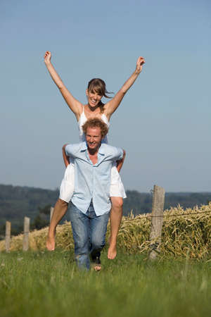 piggyback: Germany Bavaria Man giving woman piggyback in meadow laughing