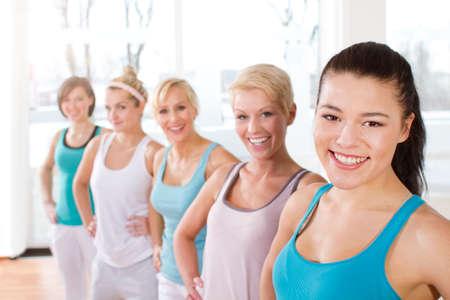 Germany Brandenburg Portrait of women standing in gym smiling LANG_EVOIMAGES