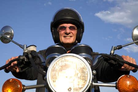 only senior adults: Man on motorbike smiling portrait LANG_EVOIMAGES