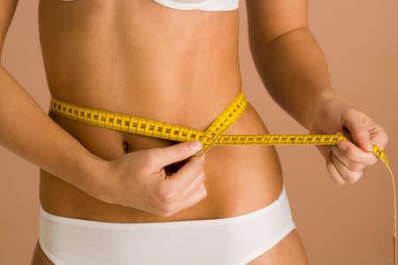 craze: Woman measuring her waist LANG_EVOIMAGES