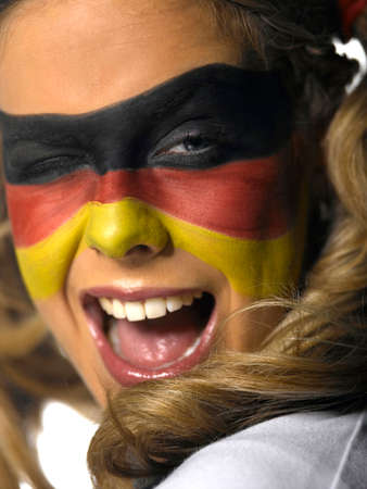 german flag: Woman with German flag painted on face winking closeup LANG_EVOIMAGES